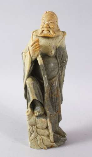 A LARGE CHINESE SOAPSTONE CARVING OF AN IMMORTAL, stood upon...
