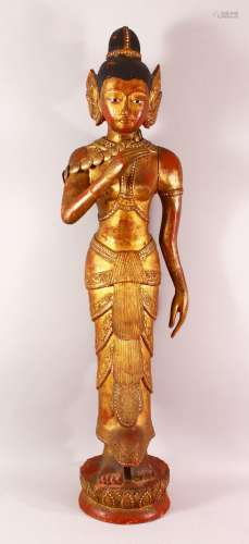 A LARGE THAI GILT AND RED LACQUER CARVED WOOD FIGURE, standi...