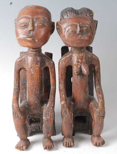 * A pair of King and Queen figures, each in seated pose with...