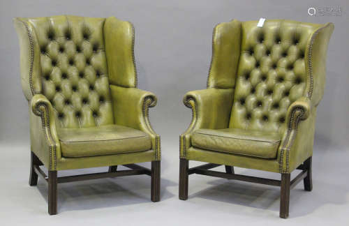 A pair of 20th century George III style wing back armchairs,...
