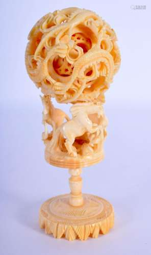 AN EARLY 20TH CENTURY CHINESE CARVED IVORY PUZZLE BALL ON ST...