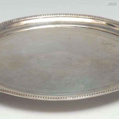 Un support de théière ovale en argent de George III, entouré...