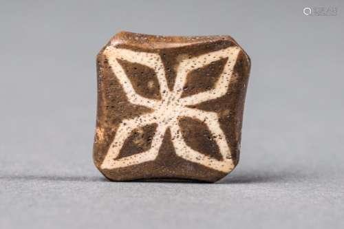 Perle quadrangulaire plate marquée du symbole Viçvavajra, le plus puissant symbole de méditation dans le rituel du Bouddhisme Tibétain. 10 éme à  11 ème siècle.   1,8 cm.