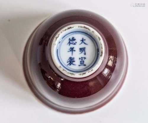 Coupelle haute sur pied en couronne en porcelaine à glaçure monochrome langyao dites sang de bœuf. Marque apocryphe à la base en bleu cobalt sous couverte de l'Empereur Xuande. Chine. Dynastie Qing.  Ht 7cm x Diam à la base 8,5cm. Ancienne collection de Mme C.