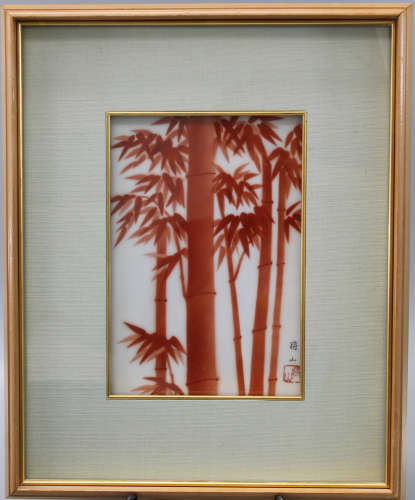 A framed Japanese porcelain plaque with red bamboo decorations.
