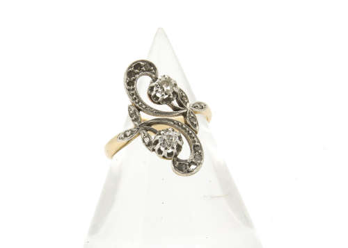 An art nouveau diamond set crossover dress ring, the claw set old cut diamonds within a floral
