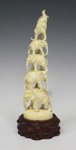 A Japanese ivory okimono figure group, Meiji period, carved and pierced with five balancing