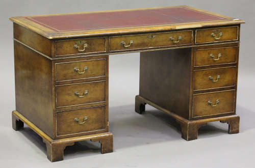 A 20th century reproduction walnut twin pedestal desk, the top inset with a gilt-tooled red
