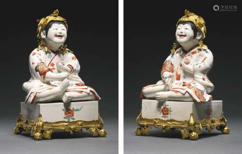 A pair of Kakiemon models of Karako (Chinese Boys) seated on Go Boards with french gilt-bronze mounts,the porcelain, Edo period (late 17th century), the gilt-bronze mounts, first half 18th century
