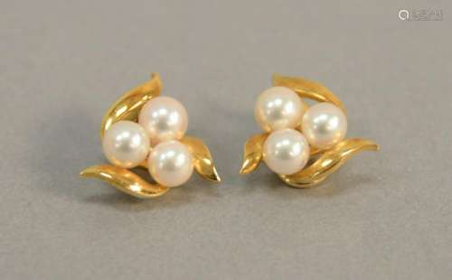 Pair of 18K gold earrings set with three pearls each,